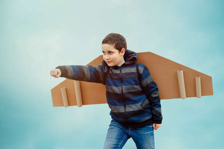 Pretty boy play with toy plane. Child on the blue sky background with paper wing airplane. Dreams of flying. Concept of summer holidays and vacations Foto de archivo