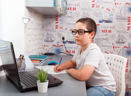 Adorable child using laptop while sitting at desk with book and doing homework. Schoolboy doing homework. Online e-learning use internet. Education, distance learning and modern technology. New normal