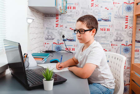 Caucasian boy using desktop computer for online study homeschooling during home quarantine. Home schooling, online study, home quarantine, online learning, corona virus or education technology concept
