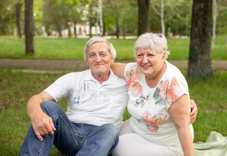 Senior woman hugging her partner and laughing together. Senior couple having fun and embracing. Caucasian elderly couples sit and relax in the park. Concept of life happily, retirement, lifestyle