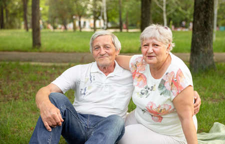 Caucasian elderly couples sit and relax in the park. Senior couple having fun and embracing. Senior woman hugging her partner and laughing together. Concept of life happily, retirement, lifestyle
