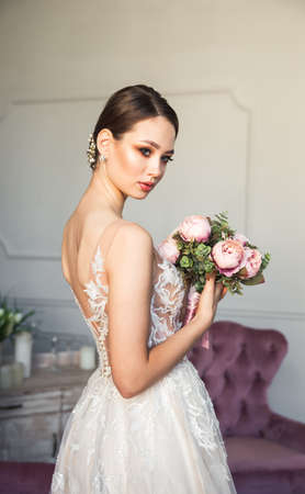 Beautiful bride posing with bouquet, fashion makeup, jewelry, hairstyle. Portrait of charming woman in wedding dress. Luxury bride, lovely lady. Studio shot of young bride in tulle dress in salon