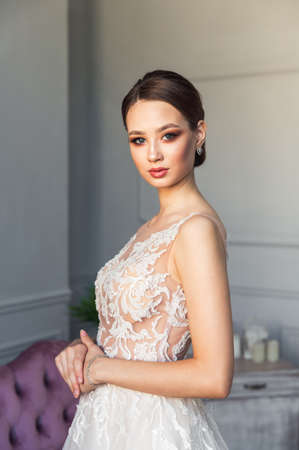 Gorgeous bride posing with bouquet, fashion makeup, jewelry, hairstyle. Portrait of charming woman in wedding dress. Happy stylish girl. Emotional lady getting ready and having fun in the morning