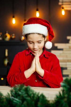 Excited little boy on Christmas day. Christmas tree. Joy and happiness. Surprised child in Santa red hat. Portrait of charming boy. Happy New Year and Xmas holiday concept. Merry Christmas your family