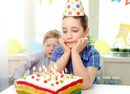Two beautiful children boys blowing candles on homemade baked cake and celebrating birthday remotely during quarantine. Beautiful adorable kids at birthday party. Making a wish on his birthday
