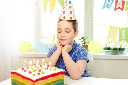 Making a wish on his birthday. Beautiful adorable eigth year old boy in blue shirt, celebrating his birthday remotely during quarantine, blowing candles on homemade baked cake. Birthday party for kids