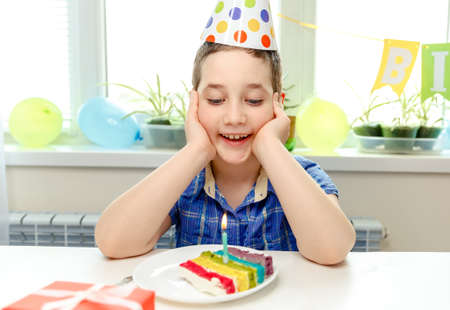 Beautiful adorable eigth year old boy in blue shirt, celebrating his birthday remotely during quarantine, blowing candles on homemade baked cake. Making a wish on his birthday. Birthday party for kids