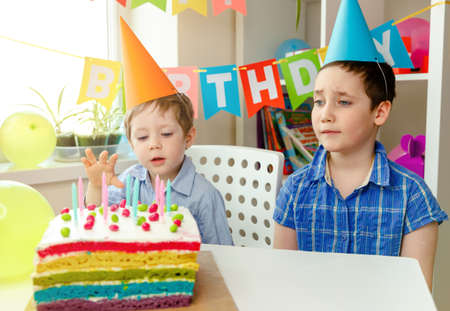 Funny brothers in party caps celebrating birthday with cake and balloons at home. Emotional children to celebrate friends birthday. Kids celebrating birthday holiday. Cute boys showing excitement Imagens