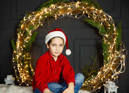 Cute boy celebrates Christmas in red cap. Photo of laughing child wearing Santa Claus hat. New Years holidays, Christmas tree. Holiday season. Free space for copy, xmas clothes, emotions, lights