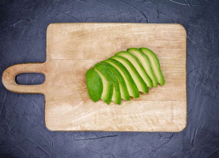 Raw cut sliced avocado on concrete background. Freshly avocado slices on wooden cutting board. Fresh ripe avocado sliced. Delicious organic fruit. Top view. Healthy food, lunch, breakfast concept