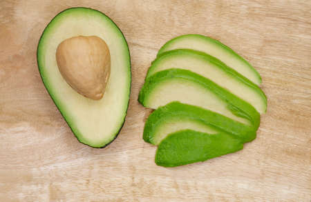 Avocado cut in the middle on a wood cutting board. Raw avocado on wooden background. Ripe avocado cut in half on a table. Tasty organic fruit. Fresh whole and sliced avocado. Healthy food concept