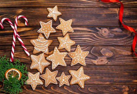 Christmas tree made from gingerbread cookies on wooden table with copy space for text. Assorted cookies. Holiday baking, celebration. New Year festive cookies with icing. Xmas postcard. Top view