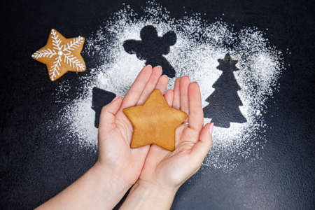 Holding gingerbread cookie in the shape of star in hands. Forms for christmas cookies. Horizontal composition of Christmas baking with flour. Making traditional gingerbread cookies. Homemade baking Reklamní fotografie