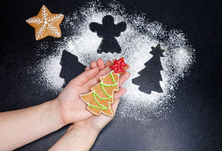 Women hands hold gingerbread cookie in the shape of a Christmas tree covered with icing sugar. Freshly cooked homemade Christmas cookies. Xmas holiday cooking, baking ingredients, pastry. Top view