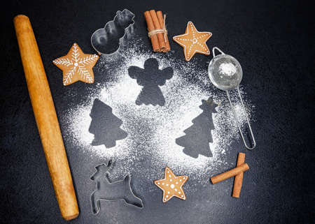 Freshly cooked homemade Christmas gingerbread cookies. Sugar powder or flour, rolling pin, cookie cutter on dark background. Holiday cooking, baking ingredients, Xmas sweet food, pastry. Top view Reklamní fotografie