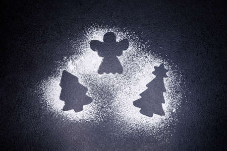 Traces from a stencil in the form of a Christmas tree and angel with snowflakes from flour on a gray concrete background. Ideas. Christmas cookies. Xmas holiday cooking, homemade baking, pastry