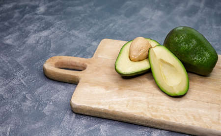 Ripe avocado cut in half on a table. Avocado is cutting in the middle on a wooden cutting board. Raw fruit on gray background. Organic avocado. Fresh whole and sliced avocado. Healthy food concept Foto de archivo
