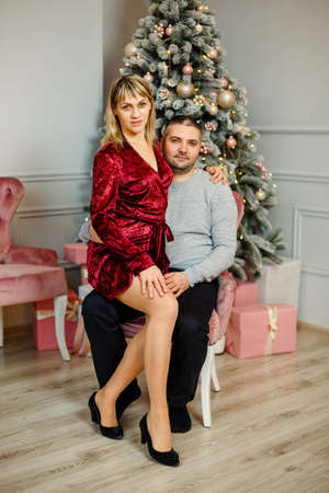 Joyful cozy moments in winter holidays. Seasonal greetings. Stylish happy couple smiling, gently hugging at christmas lights. Cute family celebrate Xmas. Beautiful young couple near the Christmas tree