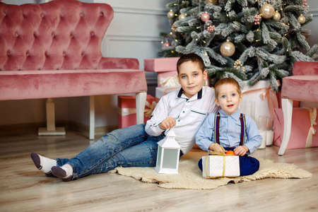 Decorated living room with traditional fireplace. Children under Christmas tree with gift boxes. Kids opening Xmas presents. Brothers having fun in living room. Cozy warm winter evening at home 版權商用圖片
