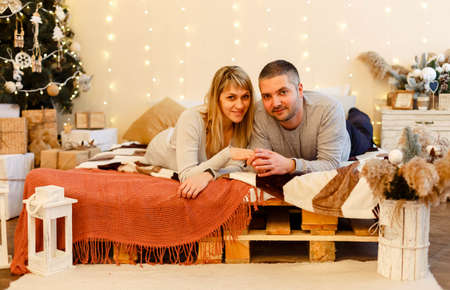 Beautiful young couple near the Christmas tree. Cute family celebrate Xmas. Joyful cozy moments in winter holidays. Seasonal greetings. Stylish happy couple smiling, gently hugging at christmas lights