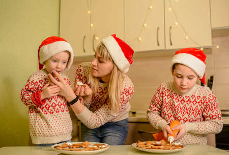 Laughing sons and cute mom are decorating homemade baked gingerbread Xmas cookies, add sprinkles, enjoy process at the table in kitchen. New Year, winter holiday. Christmas party preparation concept