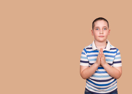 Calm boy praying to God with hands held together. Little boy praying in the morning. Portrait of kid hand praying. Hands folded in prayer concept for faith, spirituality and religion. Gratitude day