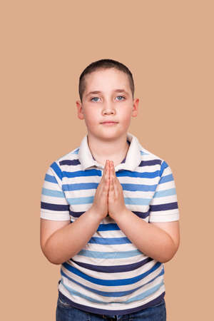 Little boy praying in the morning. Portrait of kid hand praying. Calm boy praying to God with hands held together.Hands folded in prayer concept for faith, spirituality and religion. Gratitude day