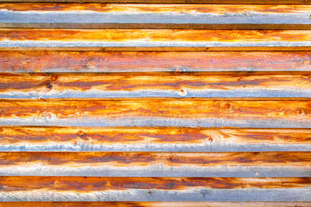 Background textured old wall of brown and orange style wooden beams. The wall of an old country house