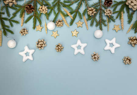 Green Christmas tree branches with New year's toys. Cones, bows and Gold stars on a sky-blue background. Space for text