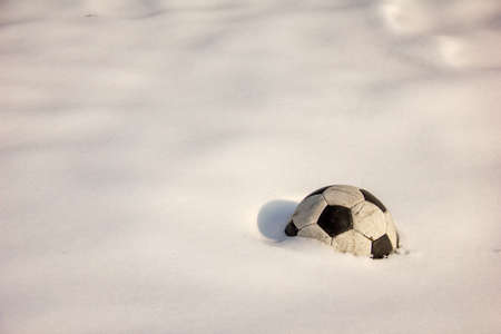 An old soccer ball lies forgotten on the white snow. The ball is covered with snow