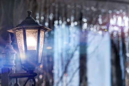 Antique frosty lamppost with blue light on the street close up on the background of the window in shining Christmas decorations sequins. Vintage glass light in night city Stock Photo