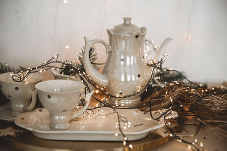 Coffee service. Vintage Teapot and cups decorated with Christmas tree branches and a glowing garland