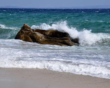 Waves crashing on rocks in stormy sea photo