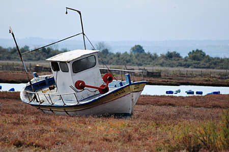grounded: wooden fishing boat grounded on river bank