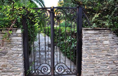 garden gate: old iron garden gate set in stone wall