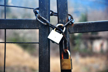 keep gate closed: black iron gate with brass padlocks