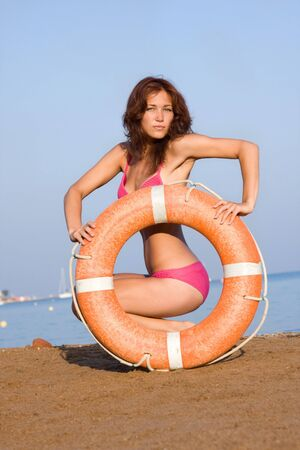 A young girl with a Life Ring on the beach  photo