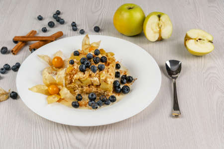 Diet, dessert. Baked apple slices with cottage cheese on a white plate on the table. physalis berries, blueberries and cinnamon sticks Stock Photo