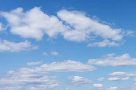 Nubi cumuliformi bianche sullo sfondo contro il blu su sfondo blu. Una limpida giornata di sole. Colori brillanti. Archivio Fotografico