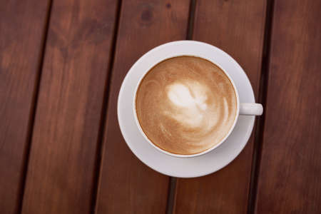 Cup of cappuccino on the wooden background. Beautiful brown foam, white ceramic cup, place for text 스톡 콘텐츠