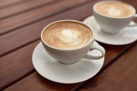 Two cups of cappuccino on the wooden background. Beautiful brown foam, white ceramic cups, place for text