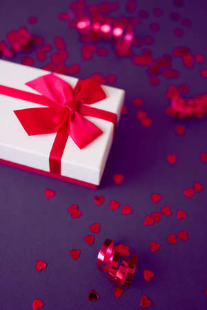 Gift box with festive ribbons on the bright purple background. Stock Photo
