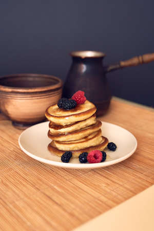 Pancakes with raspberry, mulberry and honey on the white plate.