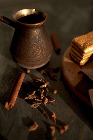 Tasty desserts, cake, coffee and cinnamon on the dark background 版權商用圖片