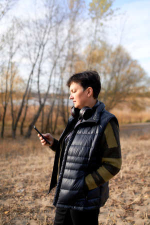 Happy mature woman walking outdoors and using smartphone