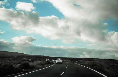 one road at the Lanzarote island, blue sky, clouds and cars coming on Редакционное