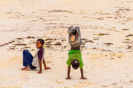Zanzibar, Tanzania, March 21, 2018. Two small african children in in the sand in tattered  smutty clothes playing for money in sunny day