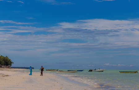 Zanzibar, Tanzania, march 21, 2018. Boy and girl are chatting in the distance while standing on the beach in national Muslim clothes standing near the ocean and boats Редакционное