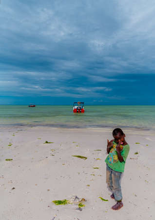 Tanzania, Zanzibar, march 21, 2018. One small african boy stands barefoot on sand in torn and dirty clothes near by water and one powerboat against.