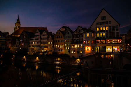 Tubingen, Tuebingen, Germany february 25, 2019. old colored houses with luminous windows in the evening on the waterfront on the background of sunset lilac sky